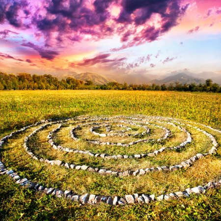 ritual: Stone spiral on the field at mountain and purple sky background in Kazakhstan, central Asia