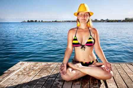 dhyana: Meditazione di giovane donna in bikini e cappello giallo sul molo a sfondo mare Archivio Fotografico