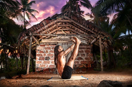 Yoga urdhva mukha paschimottanasana pose by fit man with dreadlocks on the beach near the fishermen hut in India photo