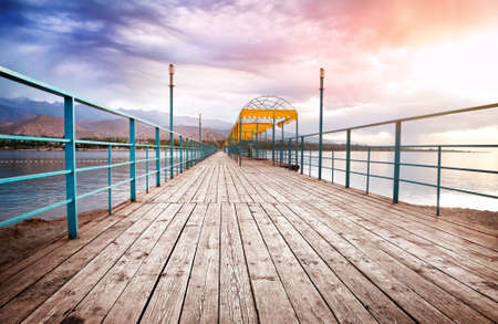 issyk kul: Pier with wooden floor at mountains and dramatic sky background in issyk kul lake, Kyrgyzstan, central Asia Stock Photo