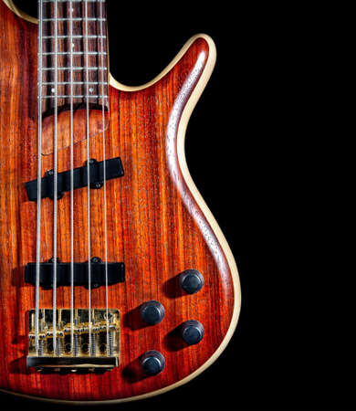 bass guitar: bass guitar from red textured wood with five strings close up isolated on black background Stock Photo