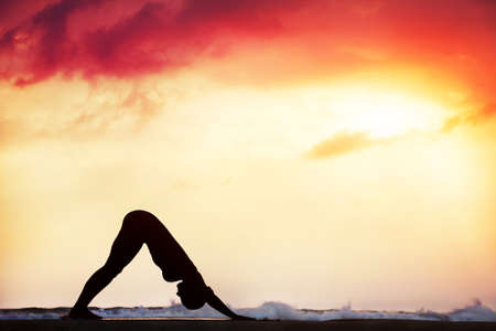 downward: Step of surya namaskar, downward facing dog pose by beautiful woman on the beach near the ocean at dramatic sunset background  Stock Photo