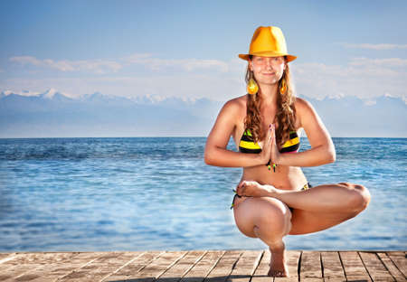hatha: Yoga balancing pose by young woman in bikini and yellow hat on the pier at sea background