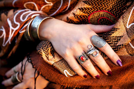 Hands with rings of tribal belly dancer at brown scarf photo