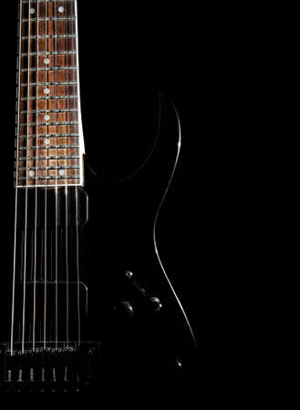 metal music: Black electric guitar with seven strings close up isolated on black background