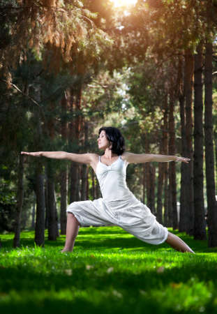 Yoga virabhadrasana II warrior pose by woman in white costume on green grass in the park around pine trees photo