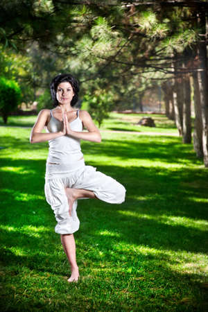 vriksasana: Yoga vrkshasana tree pose by woman in white costume on green grass in the park around pine trees