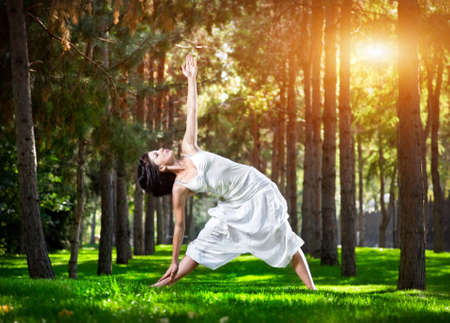 hatha: Yoga utthita trikonasana triangle pose by woman in white costume on green grass in the park around pine trees Stock Photo