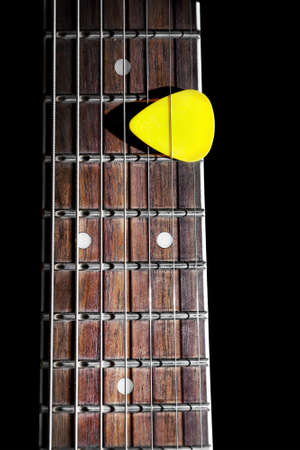 guitar: Yellow guitar pick on the fingerboard close up isolated on black background Stock Photo
