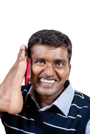 Happy Indian businessman holding cellphone by his foot and smiling at white background. Free space for your text photo