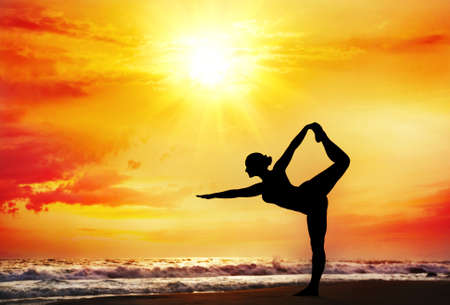 Yoga natarajasana dancer pose by woman in silhouette with dramatic sunset sky background. Free space for text