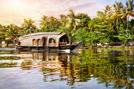 backwaters: House boat in backwaters near palms at sunrise sky in Alappuzha, Kerala, India Stock Photo