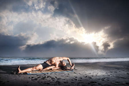 Yoga parivrtta janu sirsasana pose by fit man with dreadlocks on the beach near the ocean at sunset background photo