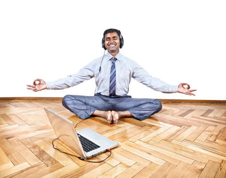 Indian businessman listening the music with headphones and doing yoga near the laptop in the office at white background. Free space for your text photo