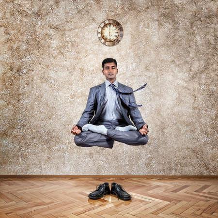 paz interior: Levitación por el empresario indio en posición de loto en la oficina cerca de la pared con el reloj y los zapatos en el suelo