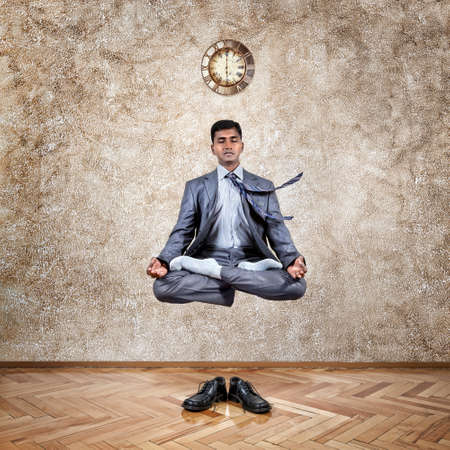inner peace: Levitation by Indian businessman in lotus pose in the office near the wall with clock and his shoes on the floor