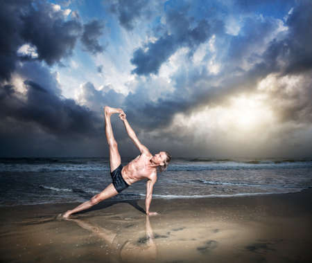 near side: Yoga vasisthasana side plank pose by fit man on the beach near the ocean at sunset background  Stock Photo