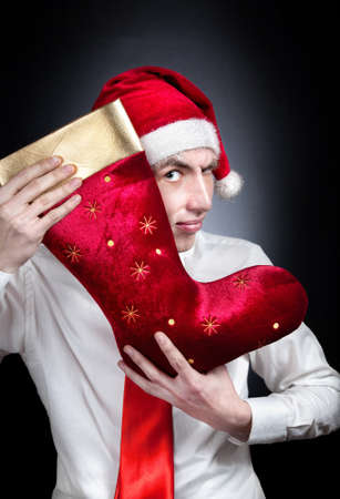 Christmas red stocking and young teen in Christmas hat and white shirt with red tie at black background photo