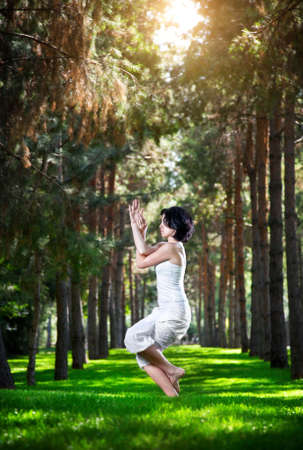 Yoga garudasana eagle pose by woman in white costume on green grass in the park around pine trees photo