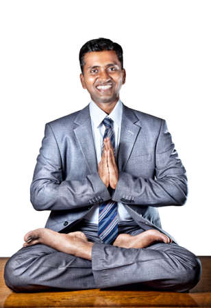Indian businessman doing yoga with big smile on the table in the office at white background. Free space for your text photo