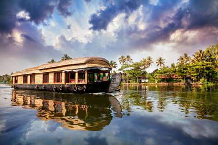 アラップザー、ケララ州、インドで曇った青空にヤシの木の近くの背水のハウスボート 写真素材