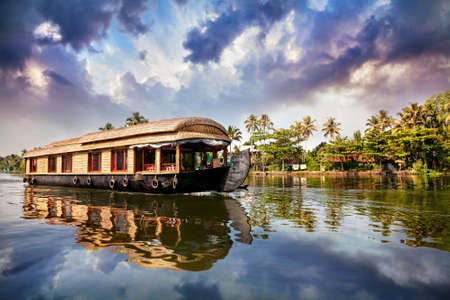 House boat in backwaters near palms at cloudy blue sky in Alappuzha, Kerala, India