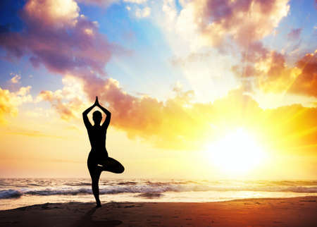 Yoga vrikshasana tree pose by woman in silhouette with sunset sky background. Free space for text photo