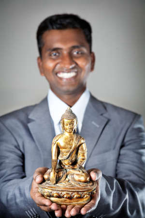 Happy Indian businessman holding bronze statue of Buddha and smiling at grey background photo