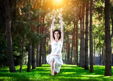 virabhadrasana: Yoga virabhadrasana I warrior pose by woman in white costume on green grass in the park around pine trees
