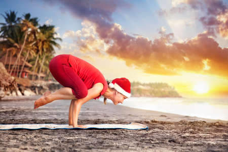 Yoga bakasana crane pose by young woman in red costume and red christmas hat on the beach near the ocean at sunset background in India