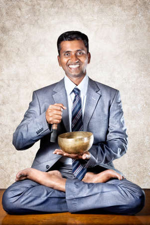 Indian businessman doing yoga meditation with Tibetan singing bowl on the table in the office at textured brown background photo