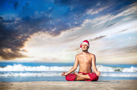 dhyana: Christmas yoga meditation in padmasana lotus pose by man in red trousers and Christmas hat on the beach near the ocean in India