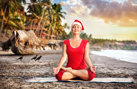 Goa: Christmas Yoga padmasana lotus pose by young woman in red costume and red christmas hat on the beach near the ocean at sunset background in India  Stock Photo
