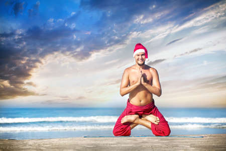 padmasana: Christmas yoga in padmasana lotus pose by happy man in red trousers and Christmas hat on the beach near the ocean in India