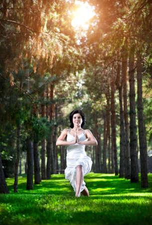 Yoga virabhadrasana I warrior pose by woman in white costume on green grass in the park around pine trees photo