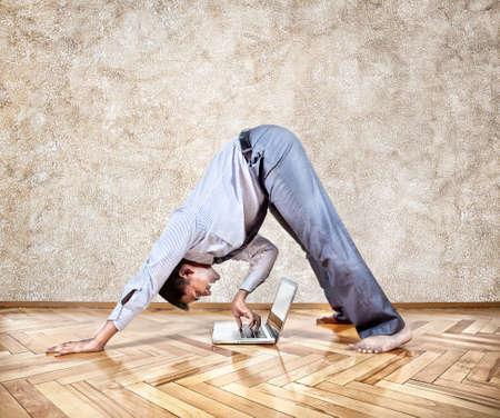 oefenen: Indische zakenman doet yoga en typen op zijn laptop in het kantoor op bruine achtergrond