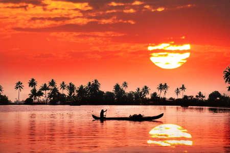 Silueta del barco y pescador en aguas estancadas en las palmas y gran fondo sol anaranjado