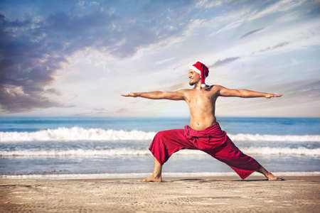 Christmas yoga warrior pose by man in red trousers and Christmas hat on the beach near the ocean in India  Stock Photo