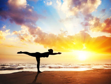 Yoga virabhadrasana III, warrior pose by woman in silhouette with sunset sky background.   Stock Photo