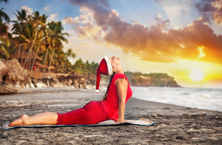 bhujangasana: Yoga cobra pose by young woman in red costume and red christmas hat on the beach near the ocean at sunset background in India