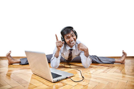 Indian businessman listening the music with headphones and doing yoga near the laptop in the office at white background. Free space for your text Stock Photo - 15941477