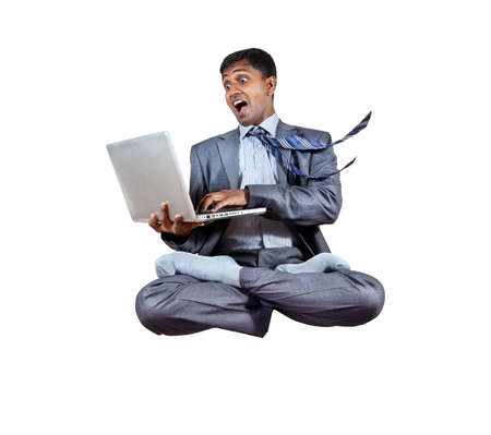 levitation: Levitation by Indian businessman with laptop in lotus pose isolated on white background. Free space for your text Stock Photo