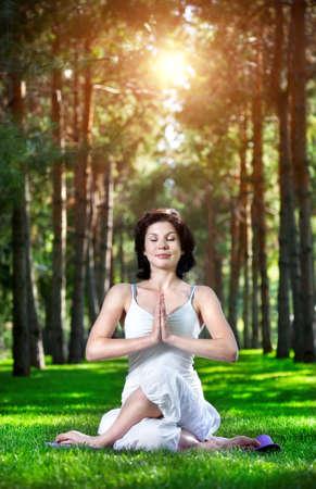 namaste: Meditaci�n Yoga en Gomukhasana pose por mujer en traje blanco sobre la hierba verde en el parque alrededor de los �rboles de pino Foto de archivo