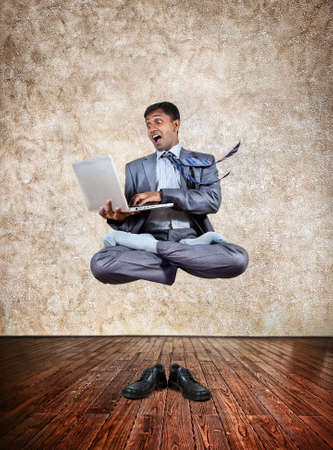Levitation by Indian businessman with laptop in lotus pose and shoes on the floor at textured background photo