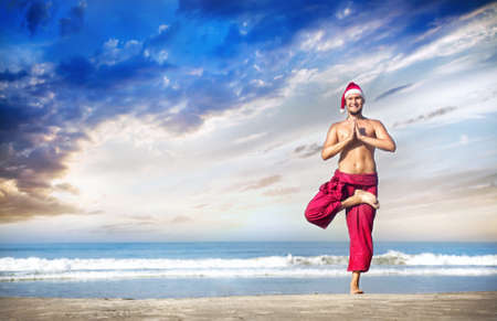vriksasana: Christmas yoga tree pose by man in red trousers and Christmas hat on the beach near the ocean in India
