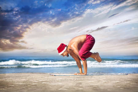 Christmas yoga bakasana crane pose by man in red trousers and Christmas hat on the beach near the ocean in India  photo