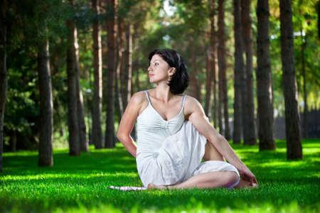 Torsión Yoga pose por mujer en traje blanco sobre la hierba verde en el parque alrededor de los árboles de pino Foto de archivo