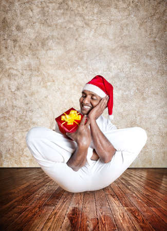 Funny Indian man in red Christmas hat doing yoga and holding red present in yoga hall with textured floor and brown background  photo