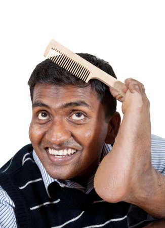 Happy Indian man holding hair brush by his foot and smiling at white background. Free space for your text photo