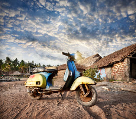 Old retro scooter on the sandy beach near fishermen huts in the tropical village in India photo